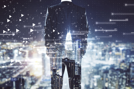 Back view of young businessman on bright night Kuala Lumpur city background with big data background. Technology and internet concept. Multiexposure