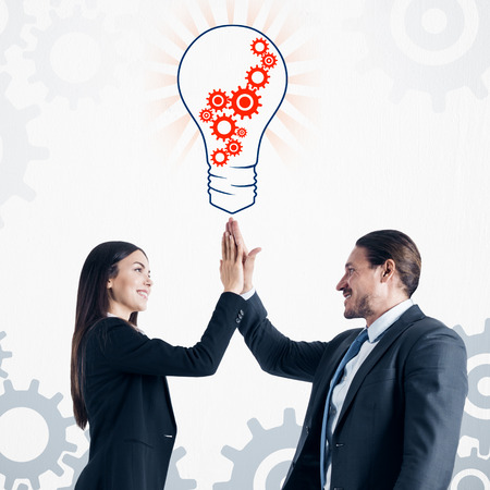 Happy european businessman and woman giving hi-fives with creative cogwheel light bulb sketch on subtle white background. Idea, innovation and teamwork concept