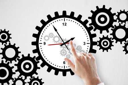 Hand pointing at creative gear cogwheel clock sketch on subtle white background. Time management concept Banco de Imagens