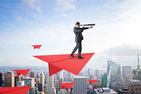 Young businessman with telescope standing on abstract red paper plane on sky and city background. Future and leadership concept