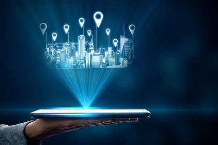Cerca de la mano que sostiene la tableta con holograma de la ciudad y pines de ubicación sobre fondo borroso con luz. Concepto de mapa e innovación Foto de archivo