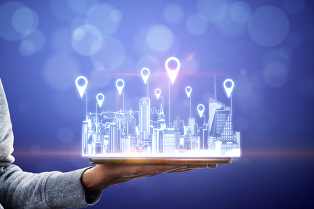 Close up of hand holding tablet with city hologram and location pins on blurry background with bokeh circles. Map and geolocation concept