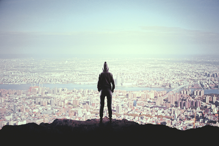 Back view of person in hoodie standing on mountain top. City background. Leadership and vision concept Stock Photo