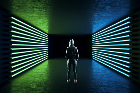 Back view of person in hoodie standing in abstract neon room interior with lamps. Design and style concept. Standard-Bild - 124293458
