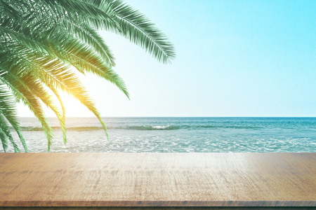 Clean wooden counter on beautiful beach and palm tree background. Mock up and Montage concept Stock Photo