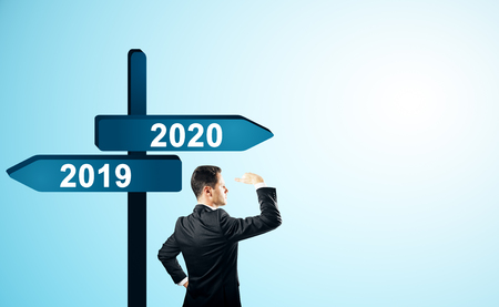 Side view of attractive man standing and looking into the distance on abstract year 2019, 2020 direction sign board on sky background. Happy New Year, research and future concept Stock Photo