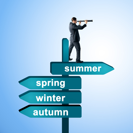 Side view of european businessman with binoculars standing and looking into the distance on abstract season direction sign board heading towards summer on blue background. Success, vision, forecast and future concept