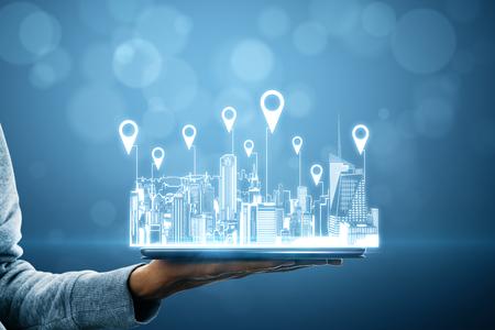 Nahaufnahme der Hand, die Tablet mit Stadthologramm und Standortstiften auf verschwommenem Hintergrund mit Bokeh-Kreisen hält. Karte und Innovationskonzept