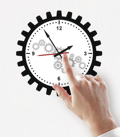 Hand pointing at creative gear cogwheel clock sketch on subtle white background. Time management and deadline concept Stock Photo