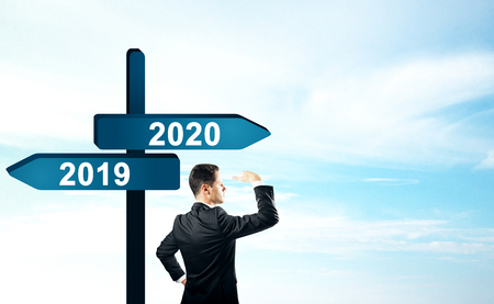 Side view of attractive businessman standing and looking into the distance on abstract year 2019, 2020 direction sign board on sky background. Happy New Year, research and future concept