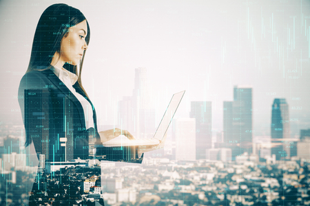 Side view of attractive young european businesswoman using laptop on blurry New York city background with forex chart. Trade and network concept. Double exposure Stock Photo