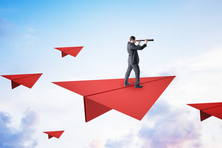 Young businessman on red paper plane looking into the distance using binoculars. Vision and research concept