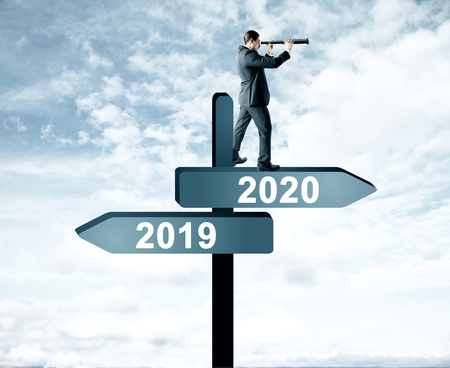 Side view of attractive man with telescope standing and looking into the distance on abstract year 2019, 2020 direction sign board on sky background. Happy New Year, research and future concept