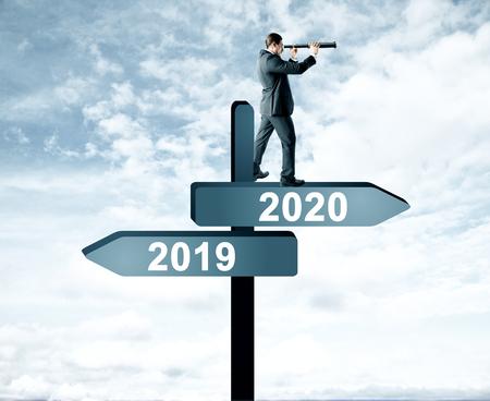 Vista lateral del hombre atractivo con telescopio de pie y mirando a lo lejos en el año abstracto 2019, 2020 tablero de señal de dirección sobre fondo de cielo. Feliz año nuevo, investigación y concepto futuro