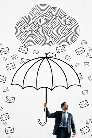 Handsome european businessman protecting himself from email cloud rain with drawn umbrella. Communication overload concept