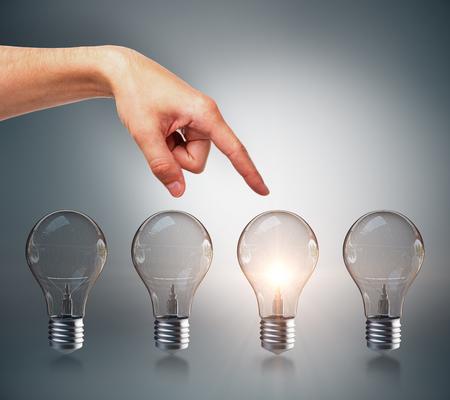 Weibliche Hand, die auf kreative Reihe von beleuchteten Glühbirnen zeigt. Auswahl, Idee und Innovationskonzept