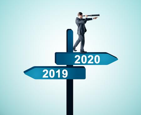 Vue latérale d'un homme d'affaires attrayant avec un télescope debout et regardant au loin sur l'année abstraite 2019, panneau de direction 2020 sur fond de ciel. Bonne année, concept de recherche et de réussite