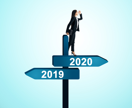 Side view of attractive woman standing on abstract year 2019, 2020 direction sign board on sky background. Happy New Year and future concept