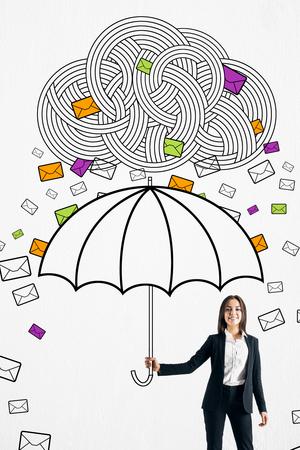 Glückliche junge Geschäftsfrau, die sich mit gezogenem Regenschirm vor E-Mail-Wolkenregen schützt. Kommunikationsüberlastungskonzept