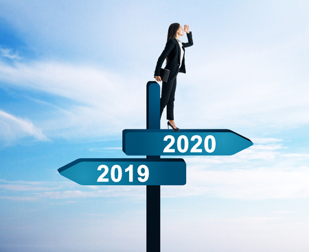 Side view of attractive businesswoman standing on abstract year 2019, 2020 direction sign board on sky background. Happy New Year and future concept
