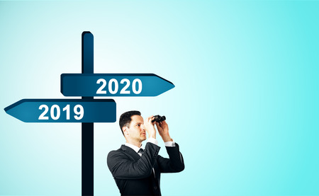 Man looking into the distance on abstract background with seas2019, 2020 sign post. New Year and future concept