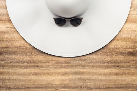 Top view of white designer beach hat and sunglasses on wooden desktop. Holiday, vacation and accessory concept. 3D Rendering Stock Photo