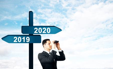 Geschäftsmann, der auf abstraktem Hintergrund mit Seas2019, 2020-Schild in die Ferne schaut. Neujahr und Zukunftskonzept