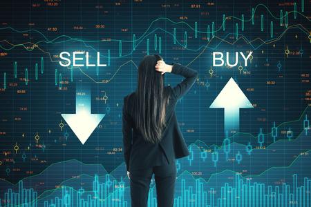 Vue arrière d'une femme d'affaires réfléchie sur fond de graphique forex achat vente créatif. Concept de marché et de commerce Banque d'images