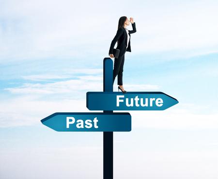 Geschäftsfrau, die auf abstrakten Hintergrund mit zukünftigen und vergangenen Wegweisern in die Ferne schaut. Erfolgs- und Prognosekonzept Standard-Bild