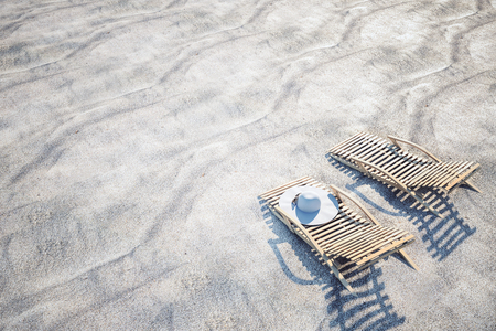 Chaise longues, beach hat and shadow on beach sand. Vacation and summer concept. 3D Rendering Stock Photo - 124294328