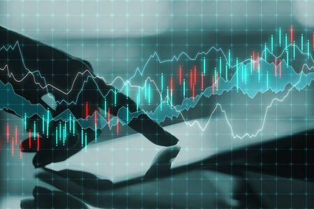 Analytics and finance concept. Close up of hand using tablet with forex chart on desktop and blurry background. Multiexposure Stock Photo