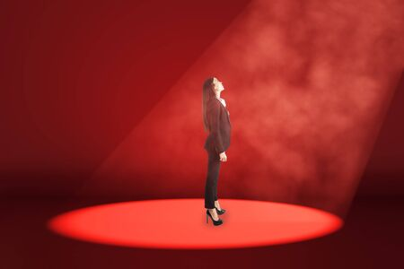 Side view of young businesswoman stansing in spot lighting in red interior. Choice and leadership concept