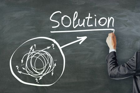 Solution and choice concept. Businessman hand drawing creative arrow doodle on chalkboard background