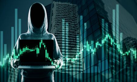 Hacker in hoodie holding laptop with glowing forex chart. Attack and stats concept. Double exposure Stock Photo
