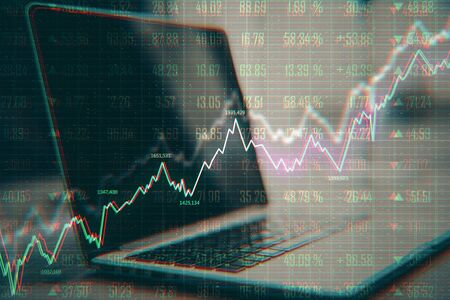 Analytics and trade concept. Close up of laptop with forex chart on desktop and blurry background. Double exposure