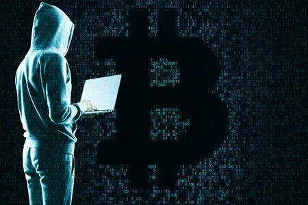 Hacking and cryptocurrency concept. Hacker using laptop with creative coding bitcoin sign Stock Photo
