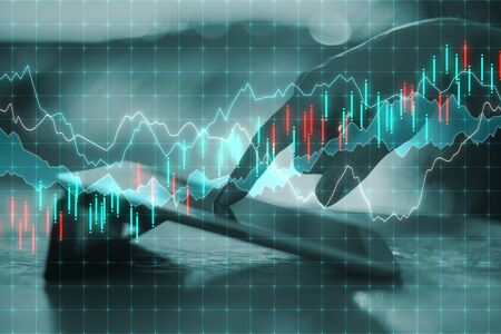 Analytics and finance concept. Close up of hand using touchpad with forex chart on desktop and blurry background. Double exposure Stock Photo