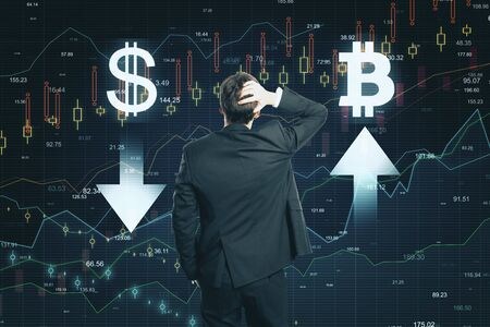 Market and cryptocurrency concept. Back view of thoughtful young businessman making decision on abstract forex chart grid background
