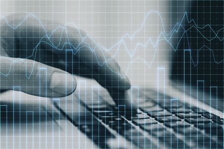 Analytics and trade concept. Close up of hands using laptop with forex chart on desktop and blurry background. Multiexposure 写真素材