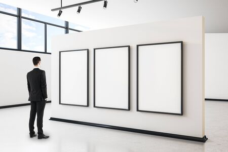 Businessman in modern gallery interior with city view, empty poster and daylight. Mock up, 免版税图像