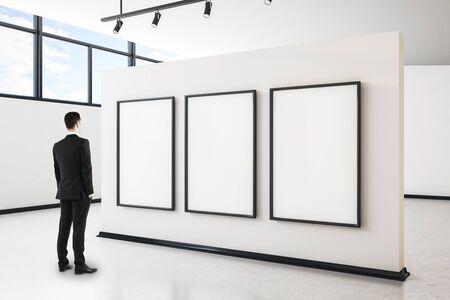 Hombre de negocios en el interior de la galería moderna con vista a la ciudad, cartel vacío y luz natural. Bosquejo, Foto de archivo