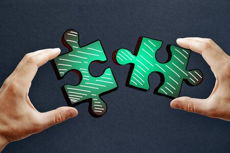 Hands holding drawn green puzzle pieces on subtle paper background. Teamwork and jigsaw concept 写真素材