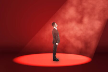 Side view of young businessman stansing in spot lighting in red interior. Choice and leadership concept