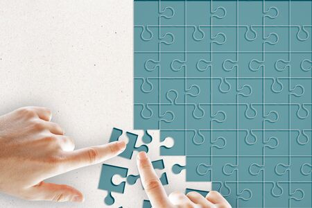 Hand assembling blue puzzles on light background. Teamwork and solution concept