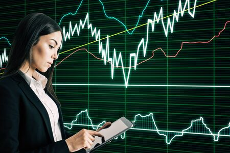 Attractive young european businesswoman using tablet with forex chart interface on blurry background. Trade and technology concept