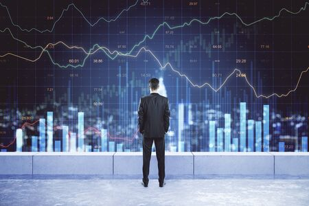 Back view of young businessman on rooftop looking at forex chart and night city view. Finance and stats concept. Multiexposure