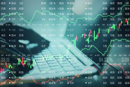 Close up of hands using laptop with forex chart. Stock and trade concept. Multiexposure