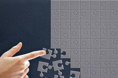 Hand assembling grey puzzles on blue background. Teamwork and solution concept