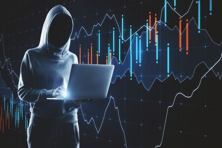 Hacker in hoodie using laptop with glowing forex chart. Virus attack and finance concept