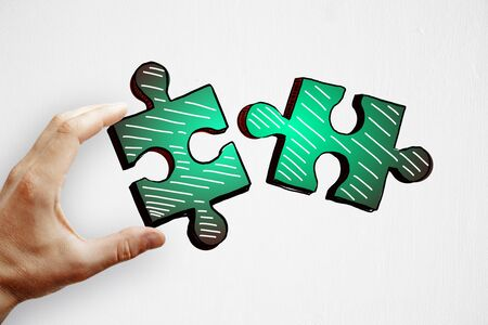 Hands holding drawn green puzzle pieces on subtle paper background. Teamwork and partnership concept